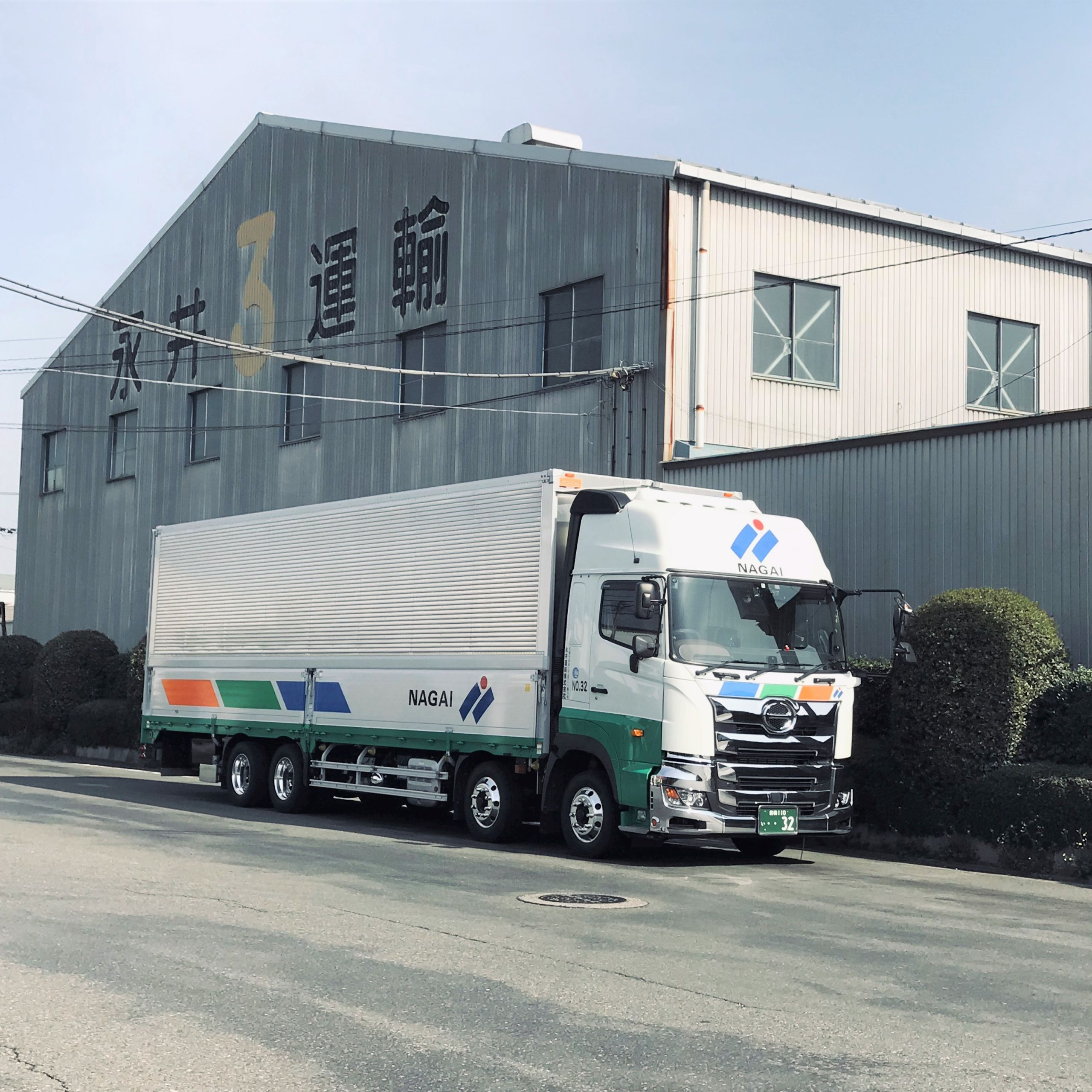 Nagai Un yu Wing body truck parked in front warehouse